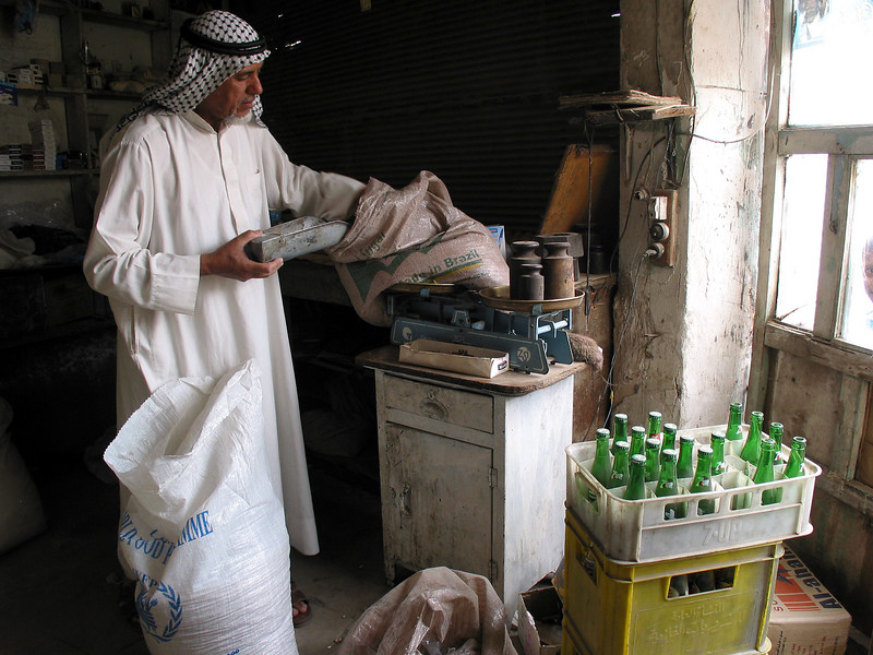 A shop keeper balances rice in Baghdad, Iraq.  Iraqis, faced with post-war and post-Saddam difficulties in restoring public services, are attempting to lead normal lives.(Australfoto/Douglas Engle)