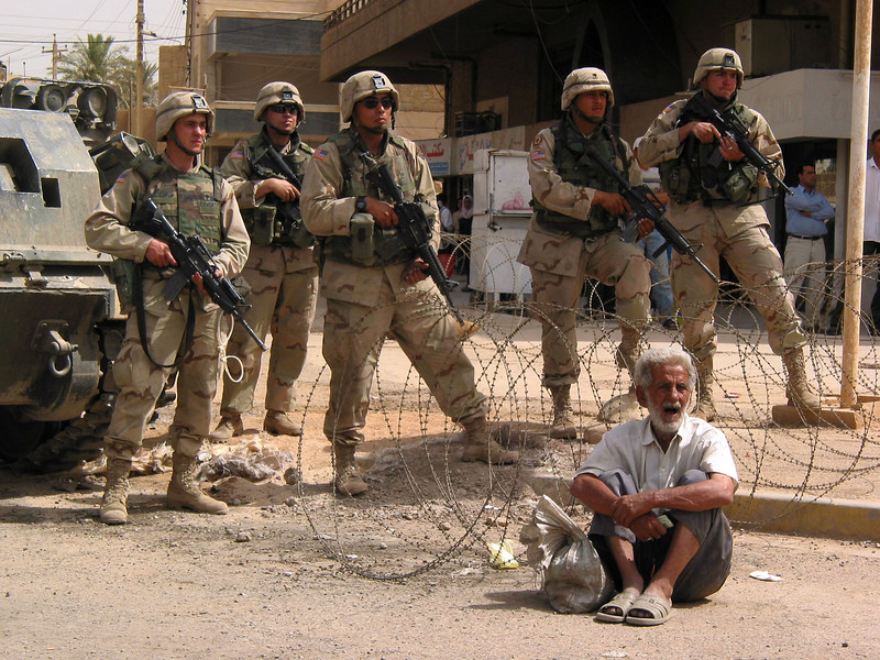 American soldiers stand behind razor wire as they watch a protest for the release of Islamic religious leader Jassim Al Saedi, in custody of US troops, in Baghdad, Iraq. The US military is finding that invading a nation is easier than ruling it.(Australfoto/Douglas Engle)