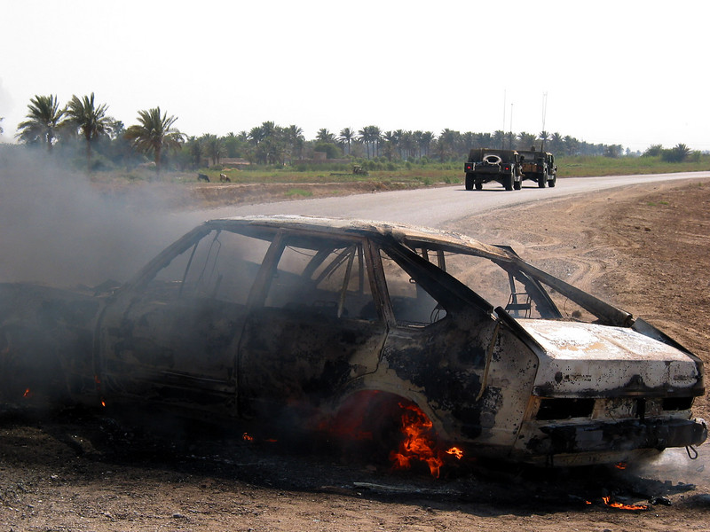 American humvees drive past a burning car south of Baghdad, Iraq. Locals said a car had been shot in the area after failing to stop for soldiers, but the soldiers said they thought the burning car was an ambush attempt.(Australfoto/Douglas Engle)