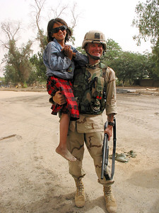 A US soldier holds a child and shotgun in Baghdad, Iraq. The US military is finding that governing a nation is much more work than taking it over.(Australfoto/Douglas Engle)
