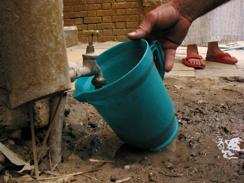 A man collects water from a spiggot in Baghdad, Iraq. Water and other services are still in short supply as Baghdad recovers from the US invasion.(Australfoto/Douglas Engle)