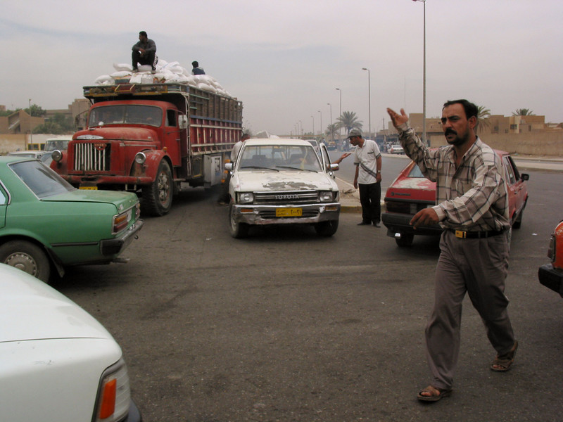 A man directs traffic at an intersection without a signal nor traffic police as UN WFP rice on a truck, back left, makes its way to distribution centers in Baghdad, Iraq, June 3, 2003.(Australfoto/Douglas Engle)