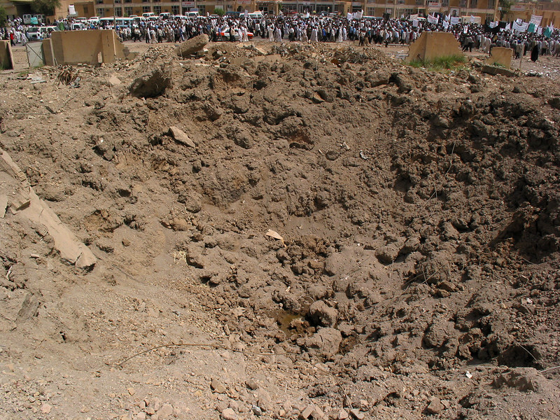 Protestors march past a bomb crater to demand the release of Islamic Shiite religious leader Jassim Al Saedi, in custody of US troops, in Baghdad, Iraq. The US military is finding that invading a nation is easier than ruling it.(Australfoto/Douglas Engle)