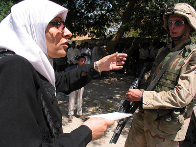 A woman tries to reason with an American soldier outside a bank in Baghdad, Iraq, Sunday, June 22, 2003. Hundreds waited hours to change 10,000 Iraqi Dinar bills, prone to counterfeiting, for smaller denominations.(Australfoto/Douglas Engle)