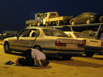 A man prays at the Jordanian Border with Iraq as hundreds of cars await the 8 am opening of the Iraqi border. Many Iraqis who have lived in exile are returning to Iraq for the first time in years.(Australfoto/Douglas Engle)
