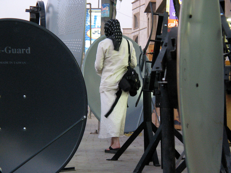 A woman walks past satellite television antennas on sale in Baghdad, Iraq. Banned during the rule of Saddam Hussein, the dishes are selling quickly as Iraqis satisfy their appetite for information and pop culture. Viewers say they like to watch music videos mostly, but Arabic language Egyptian soap operas also are a big hit.(Australfoto/Douglas Engle)