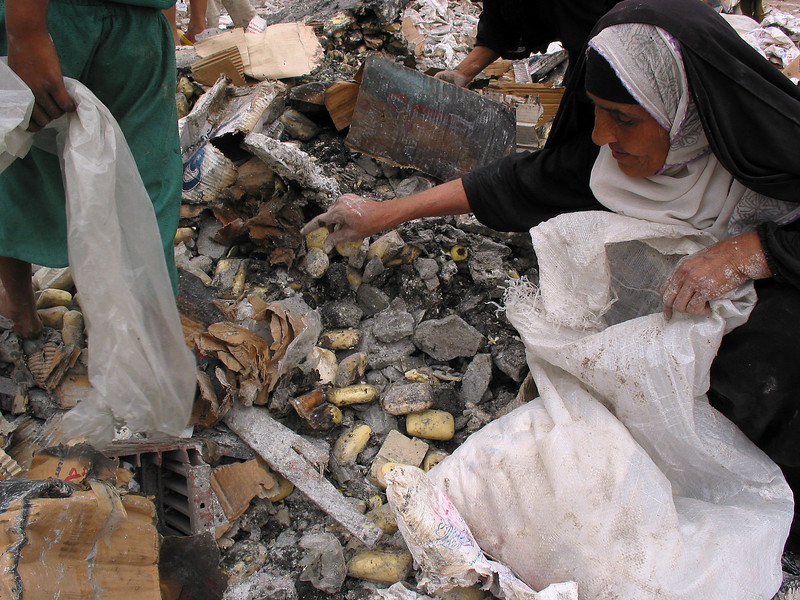 A woman salvages soap, semi destroyed from a war-time explosion in a warehouse in Baghdad, Iraq. While Saddam Hussein repressed many problems, Iraqis are now faced with the paradox of freedom and anarchy as they try to rebuild their lives. (Australfoto/Douglas Engle)