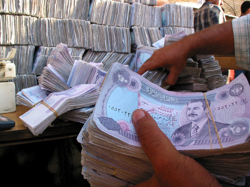 A streetside money exchanger counts Iraqi Dinars in Baghdad, Iraq. The currency, which bears the portrait of Saddam Hussein fluctuates greatly in the post-war economy. Since large notes are suspect of counterfeiting Iraqis carry large stacks of small bills.(Australfoto/Douglas Engle)