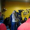 TV camera staff begin setting up.