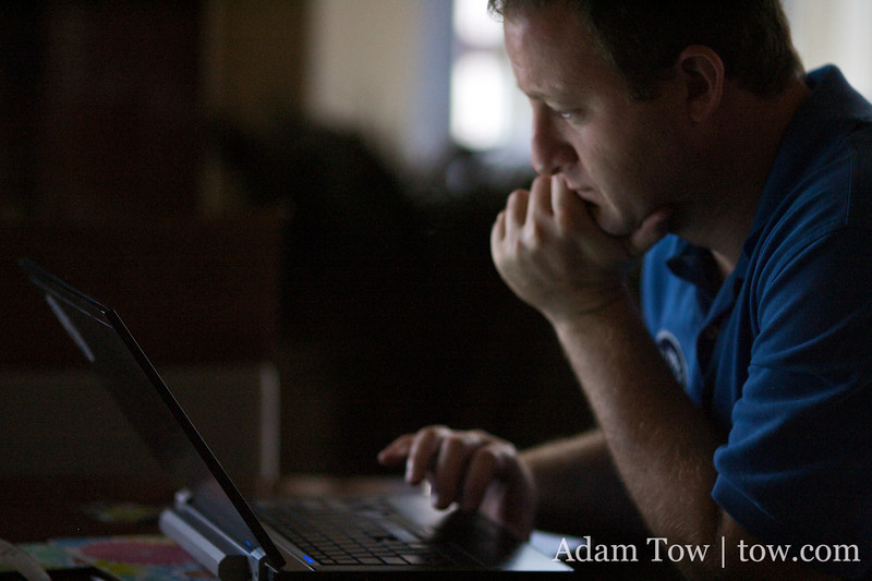 Checking email on his laptop.