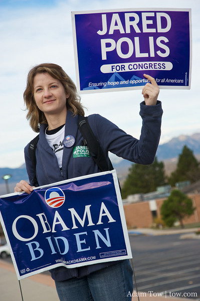 Jared's sister holds up an Obama/Biden and Polis for Congress sign.