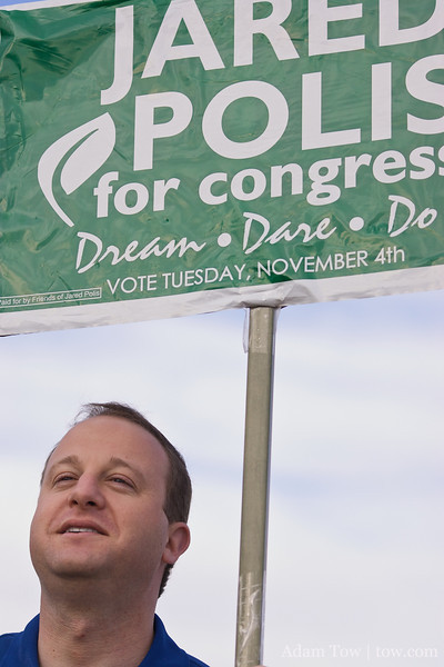 Jared holds up a Polis for Congress sign near the Westminster Church voting location.