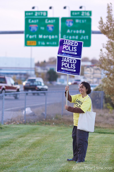Gina holds up a sign for commuters on the freeway to see.