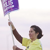 Gina waves a Jared Polis sign to highway commuters.
