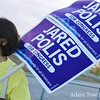 Gina holds out a double-decker Jared Polis for Congress sign.
