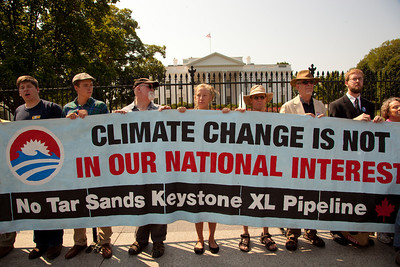 "Police arrested 65 environmentalists on August 20, 2011, outside the White House in Washington DC, as part of a demonstration urging President Obama to block the proposed Keystone XL pipeline that would bring oil from Canada's oil sands projects to Gulf Coast refineries. The proposed $7 billion, 1,700 mile pipeline needs State Department approval to proceed, and the Obama administration plans to make a decision by the end of the year. This latest act of civil disobedience was the beginning of  two weeks of White House demonstrations, with more arrests expected daily. Among those arrested on August 20 were Bill McKibben, the prominent climate activist and founder of 350.org; Gus Speth, whose career includes co-founding the Natural Resources Defense Council and chairing the White House Council on Environmental Quality in the Carter Administration; and Jane Hamsher, who founded the popular progressive blog Firedoglake. Sign reads ""Climate Change is Not in Our National Interest"". (Photo by Jeff Malet)"