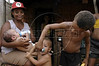 A boy gives a child a pacifier at a camp of the Landless Workers Movement (MST) in the northeastern Brazilian state of Pernambuco. The MST has ended its honeymoon with President Luiz Inacio Lula da Silva, who they supported in the 2002 election, and has begun a campaign of land invasions to speed up agrarian reform. The MST says lula is slow on reform an invasions are the only way to pressure the government. Founded in 1985, the Landless Workers Movement is the largest social movement in Latin America and one of the most successful grassroots movements in the world. Hundreds of thousands of landless peasants have taken onto themselves the task of carrying out a land reform in a country mired by an overly skewed land distribution pattern.  Less than 3% of the population owns two-thirds of Brasil's arable land.  Under Brazil's constitution, the government must redistribute farmland that is unused. Today more than 250,000 families have won land titles to over 15 million acres after MST land takeovers. (Australfoto/Douglas Engle)