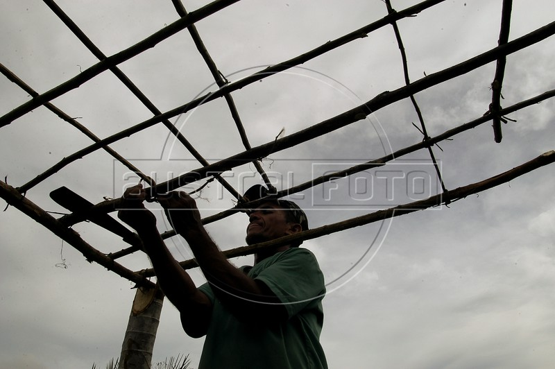 A member of the Landless Workers Movement (MST) set ups a shelter at a camp in the northeastern Brazilian state of Pernambuco. The MST has ended its honeymoon with President Luiz Inacio Lula da Silva, who they supported in the 2002 election, and has begun a campaign of land invasions to speed up agrarian reform. The MST says lula is slow on reform an invasions are the only way to pressure the government. Founded in 1985, the Landless Workers Movement is the largest social movement in Latin America and one of the most successful grassroots movements in the world. Hundreds of thousands of landless peasants have taken onto themselves the task of carrying out a land reform in a country mired by an overly skewed land distribution pattern.  Less than 3% of the population owns two-thirds of Brasil's arable land.  Under Brazil's constitution, the government must redistribute farmland that is unused. Today more than 250,000 families have won land titles to over 15 million acres after MST land takeovers. (Australfoto/Douglas Engle)