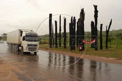 A truck passes a memorial to Landless Peasant (MST) massacre victims, made of 19 burned tree trunks, on the side of the PA-150 highway near Carajas in southern Par‡ state, Brazi. In what ins now known as the Carajas Massacre, 19 MST members were killed April 19, 1996 when state police opened fire on hundreds of protesting MST members who had blocked the highway to demand land reform. Other two victims died from the wounds some years later. (Australfoto/Douglas Engle)