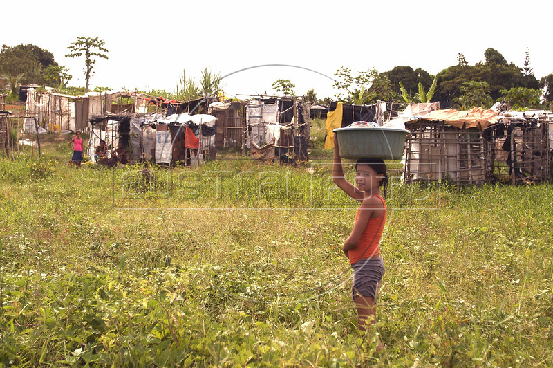 A young girl carries water at a Landless Workers Movement (MST) camp in the northeastern Brazilian state of Pernambuco. The MST has ended its honeymoon with President Luiz Inacio Lula da Silva, who they supported in the 2002 election, and has begun a campaign of land invasions to speed up agrarian reform. The MST says lula is slow on reform an invasions are the only way to pressure the government. Founded in 1985, the Landless Workers Movement is the largest social movement in Latin America and one of the most successful grassroots movements in the world. Hundreds of thousands of landless peasants have taken onto themselves the task of carrying out a land reform in a country mired by an overly skewed land distribution pattern.  Less than 3% of the population owns two-thirds of Brasil's arable land.  Under Brazil's constitution, the government must redistribute farmland that is unused. Today more than 250,000 families have won land titles to over 15 million acres after MST land takeovers. (Australfoto/Douglas Engle)<br /> Brazil, MST, agrarian reform, land, conflict, poor, poverty, economy, landless