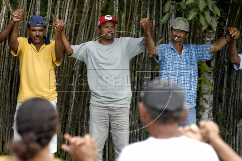 Members of the Landless Workers Movement (MST) attend a meeting at a makeshift camp in the northeastern Brazilian state of Pernambuco. The MST has ended its honeymoon with President Luiz Inacio Lula da Silva, who they supported in the 2002 election, and has begun a campaign of land invasions to speed up agrarian reform. The MST says lula is slow on reform an invasions are the only way to pressure the government. Founded in 1985, the Landless Workers Movement is the largest social movement in Latin America and one of the most successful grassroots movements in the world. Hundreds of thousands of landless peasants have taken onto themselves the task of carrying out a land reform in a country mired by an overly skewed land distribution pattern.  Less than 3% of the population owns two-thirds of Brasil's arable land.  Under Brazil's constitution, the government must redistribute farmland that is unused. Today more than 250,000 families have won land titles to over 15 million acres after MST land takeovers. (Australfoto/Douglas Engle)