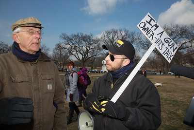 """A lone counter demonstrator shows up at a pro gun-control rally in Washington D.C. with a sign that reads,"""" I am a gun owner. Let's talk."""" 100 residents from Newtown, Connecticut and thousands of other gun-control activists gathered on Saturday, January 26, 2013 in Washington D.C. in a march down Constitution Ave. to a rally with speeches, musical performances and a poetry reading near the Washington Monument. (Photo by Jeff Malet)"""