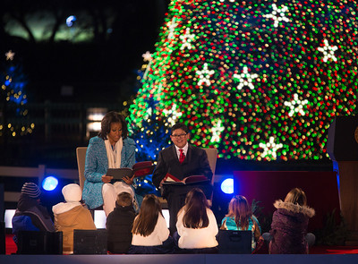 "First lady Michelle Obama, left, joined by Rico Rodriguez of ""Modern Family,"" reads ""Twas the Night Before Christmas"" to children gathered on the stage of the National Christmas Tree Lighting Ceremony on the Ellipse just south of the White House  in Washington D.C. on December 6, 2012. It was the 90th annual edition of the tree lighting ceremony. (Photo by Jeff Malet)"