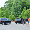 His assistants greet him on his arrival. ..Secret Service detail in both vehicles.