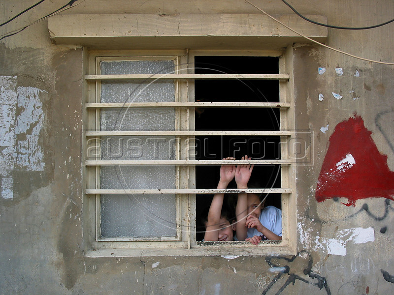 Children peer through a window at the Shatila Palestinian refugee camp in Beirut, Lebanon. Shatila and another camp were site of an infamous massacre of more than 1000 people in 1982 by Christian milita members as Israeli soldiers stood by. The UN estimates over 300,000 Palestinian refugess in Lebanon, who are denied many services and banned from working in many occupations.(Australfoto/Douglas Engle)