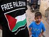 """A boy walks past another wearing a """"free Palestine"""" shirt at the Shatila Palestinian refugee camp in Beirut, Lebanon. Shatila and another camp were site of an infamous massacre of more than 1000 people in 1982 by Christina milita members as Israeli soldiers stood by. The UN estimates over 300,000 Palestinian refugess in Lebanon, who are denied many services and banned from working in many occupations.(Australfoto/Douglas Engle)"""