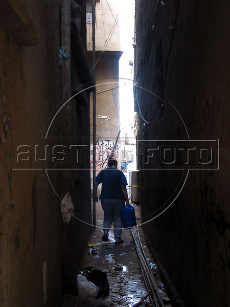 A woman carries water through a narrow passage-way at the Shatila Palestinian refugee camp in Beirut, Lebanon. Shatila and another camp were site of an infamous massacre of more than 1000 people in 1982 by Christina milita members as Israeli soldiers stood by. The UN estimates over 300,000 Palestinian refugess in Lebanon, who are denied many services and banned from working in many occupations.(Australfoto/Douglas Engle)