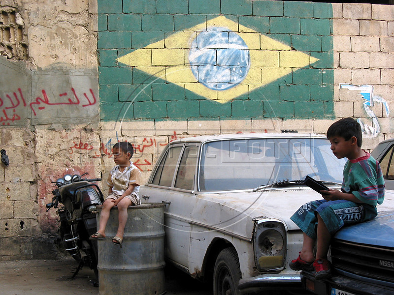 Children sit in front of a Brazilian flag, left over from the 2002 World Cup, at the Shatila Palestinian refugee camp in Beirut, Lebanon. Shatila and another camp were site of an infamous massacre of more than 1000 people in 1982 by Christian milita members as Israeli soldiers stood by. The UN estimates over 300,000 Palestinian refugess in Lebanon, who are denied many services and banned from working in many occupations.(Australfoto/Douglas Engle)