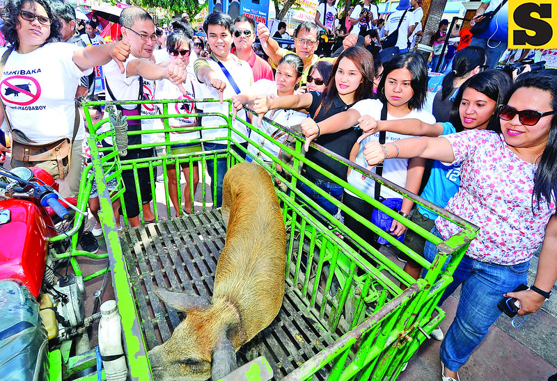 DAVAO. Media practitioners in Davao City show unity as they make a thumbs down sign at a live pig that was used as a symbol of pork barrel during a protest against misuse of Priority Development Assistance Fund along with other groups and sectors at Rizal Park on Monday. (King Rodriguez photo/Sun.Star Davao)