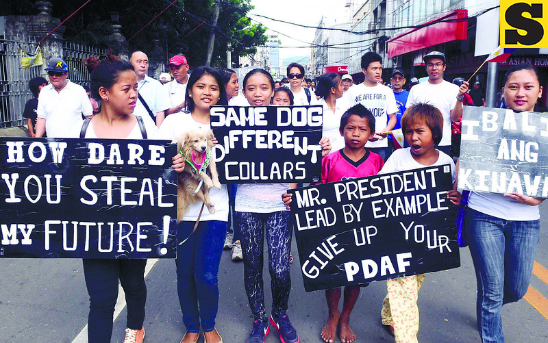 Members of a youth group carry anti-pork barrel messages in the rally on Monday that started at the Fuente Osmeña and ended at the Plaza Independencia in Cebu City. (Arni Aclao photo/Sun.Star Cebu)