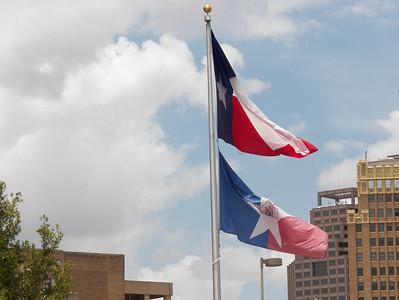 Texas Flag and San Antonio flags wave proudly in downtown San Antonio.