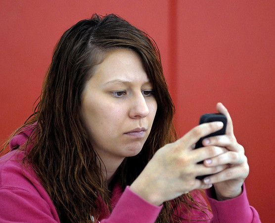 Ward 1, precinct 7 clerk Courtney Miller texts while passing time between voters showing up at East Side Intermediate School.