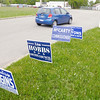 A car passes election signs as it leaves Anderson Elementary during the primary election on Tuesday.