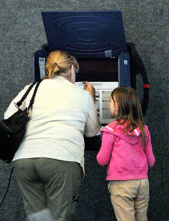 Karen Myers explains the voting process to her granddaughter Keely Myers, 8, as she casts her ballot in ward 3, precinct 2 at Main Street Church of God.