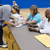 Neda Watson signs in before voting at precinct 4-3 at Anderson Elementary School as clerks Debbie Cole, left, and Alean Wallace look on during the Primary election on Tuesday.