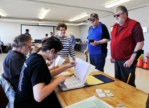 John P. Cleary   The Herald Bulletin<br /> Ward 1, Precinct 1 workers check the poll book for these voters at  the National Guard Armory.