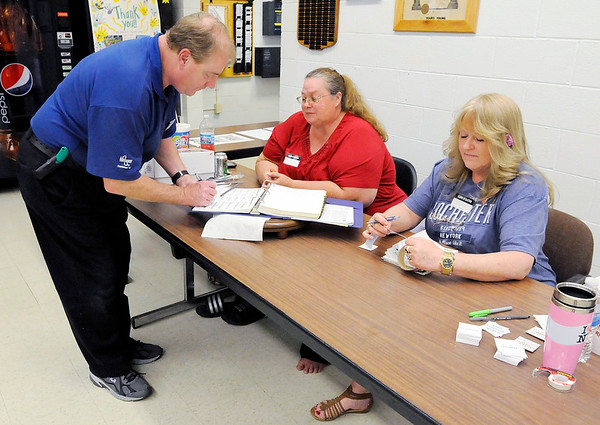 Don Knight   The Herald Bulletin<br /> Paul Schrenker signs in with clerks Rhonda Hurt and Tari Franklin before voting at the Central Services Building on Tuesday.
