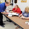 Don Knight | The Herald Bulletin<br /> Paul Schrenker signs in with clerks Rhonda Hurt and Tari Franklin before voting at the Central Services Building on Tuesday.