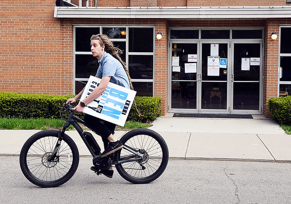 John P. Cleary | The Herald Bulletin <br /> Democrat candidate for Anderson City Council District 4 Ben Orcutt delivers one of his signs to the Fifth Street United Methodist Church voting site Tuesday morning on his bike.