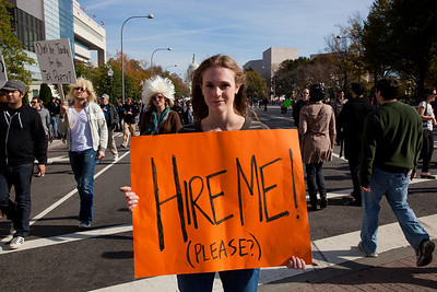 """Hire Me"" says Christine Fitzpatrick who lives in the DC area. Imaginative protest signs were ubiquitous among the several hundred thousand who attended a ""Rally to Restore Sanity and/or Fear"" on the National Mall organized by Comedy Central talk show hosts Jon Stewart and Stephen Colbert  in Washington DC on Saturday, October 30, 2010. The rally took place only a few days before crucial mid-term elections that could tilt power in Congress toward the Republicans. The high level of unemployment, hovering just under 10%, will weigh heavily. (Photo by Jeff Malet)"