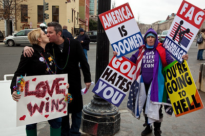 """Newlyweds Morgan Murphy and Todd Williamson from DC. hold Love Wins sign amid anti gay protestors. They are a straight couple that had """"boycotted marriage for 6 years until everyone can marry and today's the first day""""."""