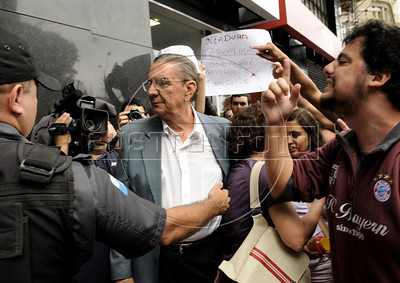"""Politic activists shout """"torturer"""" and """"murderer,"""" at retired military men arriving at a military club in downtown to celebrate the anniversary of 1964 military coup, Rio de Janeiro, Brazil, March 29, 2012. In the poster says """"Don't ceklebrate torture"""". A club of retired military officers celebrates annualy lheld the Brazil's 1964 military coup, but faced protestors as members arrived for the event. (Austral Foto/Renzo Gostoli)"""