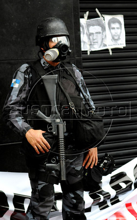 Riot policeman stands guard following clashes with protesters during a demonstration against retired military men leaving a military club in downtown to celebrate the anniversary of 1964 military coup, Rio de Janeiro, Brazil, March 29, 2012. A club of retired military officers celebrates annualy lheld the Brazil's 1964 military coup, but faced protestors as members arrived for the event. (Austral Foto/Renzo Gostoli)