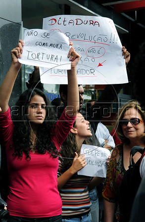 """Politic activists shout """"torturer"""" and """"murderer,"""" at retired military men arriving at a military club in downtown to celebrate the anniversary of 1964 military coup, Rio de Janeiro, Brazil, March 29, 2012. In the right of the photo stay Brazilian journalist Hildegard Angel, whose mother and brother were victims (murdered) of military dictatorship. A club of retired military officers celebrates annualy lheld the Brazil's 1964 military coup, but faced protestors as members arrived for the event. (Austral Foto/Renzo Gostoli)"""