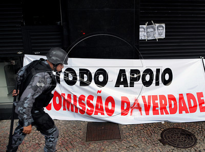 A policeman past by a banner defending a formal investigation into the 20-year brazilian dictatorshi during a protest against celebrations by retired military men at a military club in downtown, Rio de Janeiro, Brazil, March 29, 2012. A club of retired military officers celebrates annualy the Brazil's 1964 military coup, but faced protestors as members arrived for the event. (Austral Foto/Renzo Gostoli)