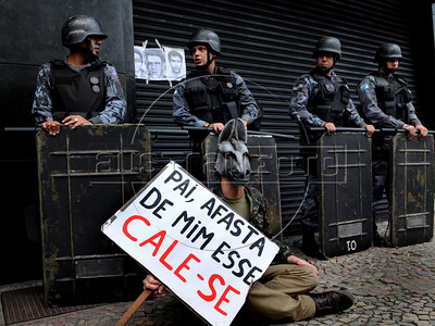 A student wearing a donkey mask and a military camuflaged shirt seats on the sidewalk holding a poster with a line of Brazilian singer song writer Chico Buarque during a protest against a celebration of the anniversary of 1964 military coup by retired military, Rio de Janeiro, Brazil, March 29, 2012. A club of retired military officers celebrates annualy lheld the Brazil's 1964 military coup, but faced protestors as members arrived for the event. (Austral Foto/Renzo Gostoli)